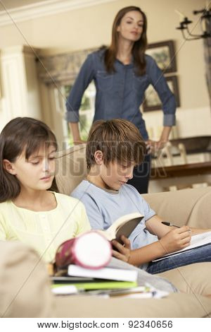 Two Children With Homework Sitting On Sofa At Home Whilst Mother Watches