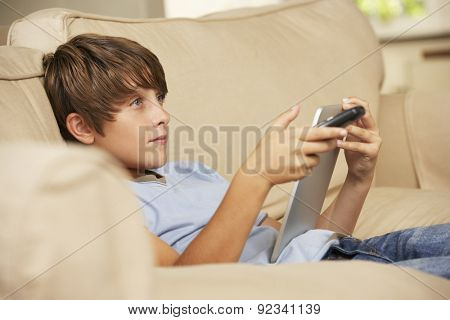Young Boy Sitting On Sofa At Home Using Tablet Computer Whilst Watching Television
