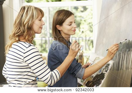 Female Artist Teaching Pupil In Studio