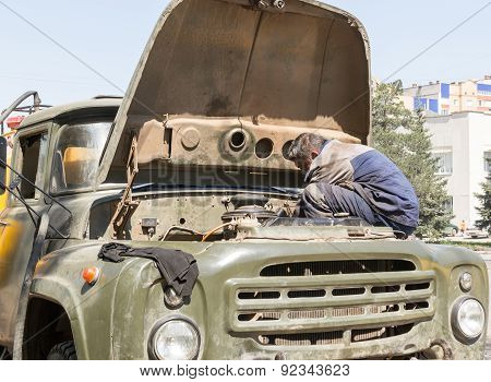 Worker Fixing Vehicle Engine