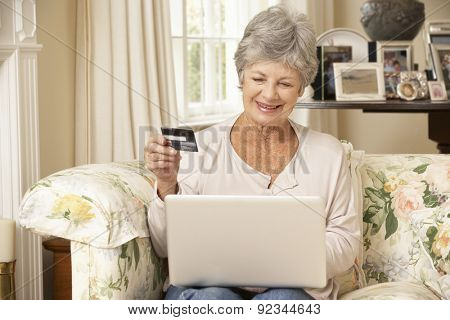 Retired Senior Woman Sitting On Sofa At Home Using Laptop To Make Online Purchase