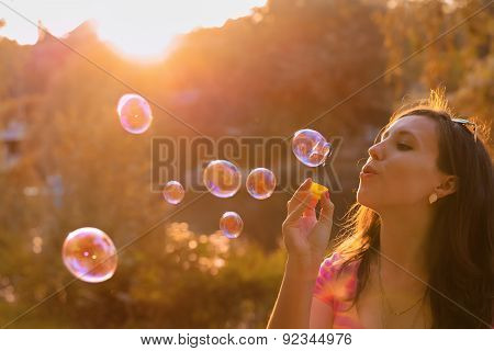 Girl Blowing Soap Bubbles At Sunset