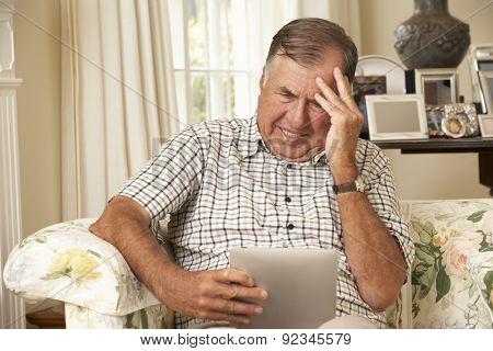Frustrated Retired Senior Man Sitting On Sofa At Home Using Digital Tablet