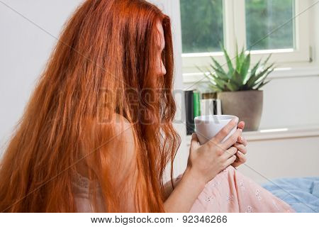 Pensive Woman Having An Early Coffee At Her Bed