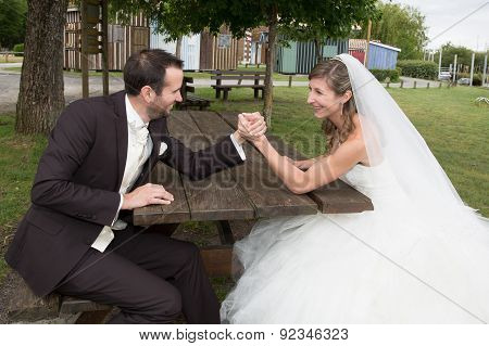 Young Happy Newly Wed Couple  Fighting In Arm Wrestling