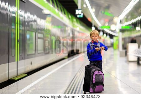 little boy waiting for the train on tube platform