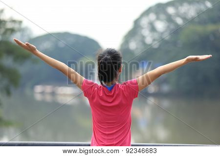 cheering young asian woman open arms on bridge
