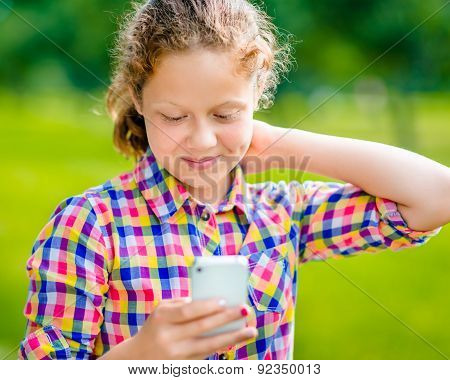 Beautiful Smiling Teenage Girl In Casual Clothes With Smartphone In Her Hand, Looking At Screen