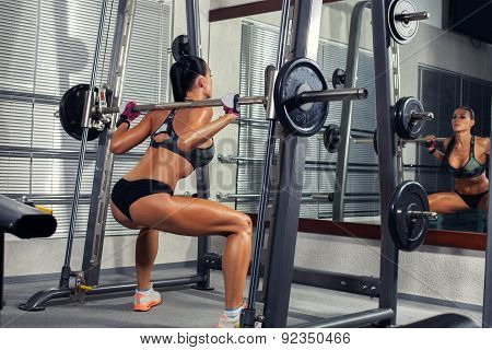 beautiful sports fitness girl with a barbell in the gym, crouche