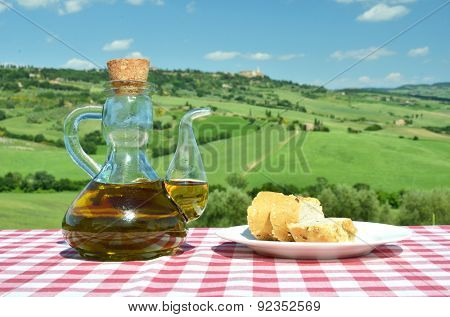 Olive oil and bread against on the checkered cloth against Tuscan landscape. Italy