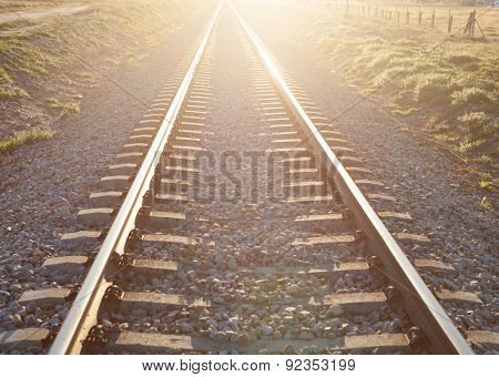 Railroad track sunlit with a beautiful sunset