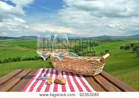 Two wineglasses and cantuccini on the wooden table Tuscan landscape, Italy