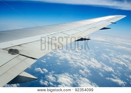 Wing of an airplane with a nice aerial view of the sky with clouds