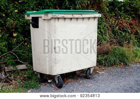 Waste container with green lid on the street