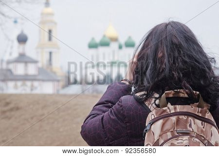 Back view of hiking woman is holding camera taking photographs