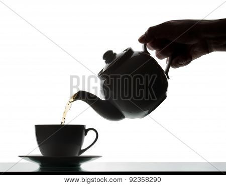 Teapot Pouring Tea Into A Cup. Silhouette