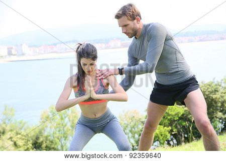 Fitness girl with coach working out in outdoor park