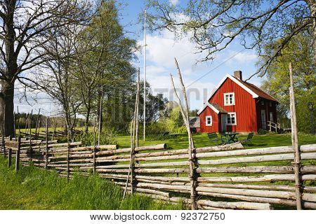 old farm and wooden fence set in a rural spring landscape, Sweden