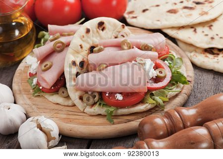 Piadina romagnola, italian flatbread sandwich with rocket salad, ricotta cheese and baloney