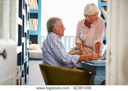 Senior Couple In Home Office Looking At Laptop