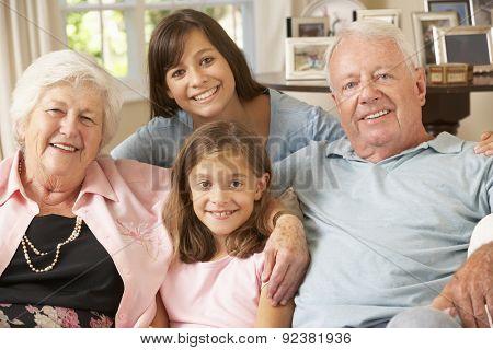 Grandparents Sitting On Sofa With Grandchildren Indoors
