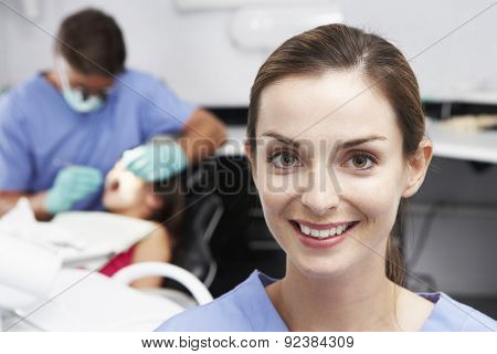 Portrait Of Dental Nurse With Dentist Examining Patient In Background