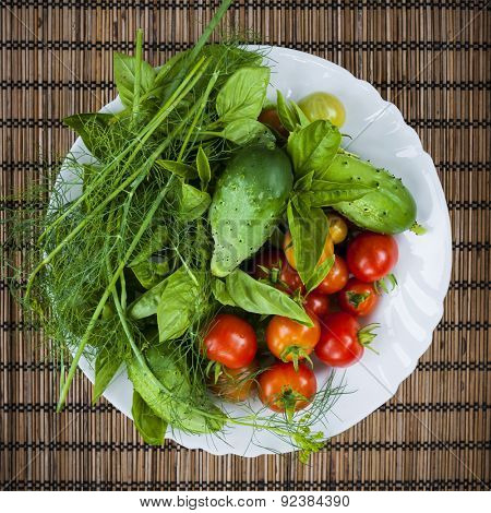 Fresh vegetables and herbs picked from garden in bowl, overhead view
