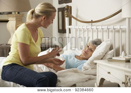 Adult Daughter Giving Senior Female Parent Medication In Bed At Home