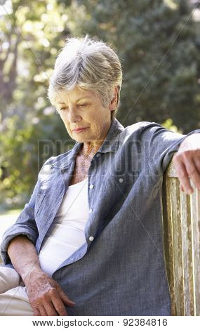 Unhappy Senior Woman Sitting On Park Bench