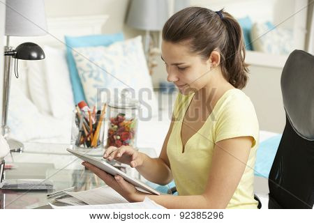 Teenage Girl Studying At Desk In Bedroom Using Digital Tablet