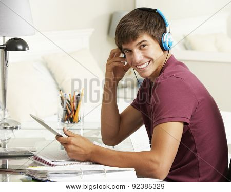 Teenage Boy Studying At Desk In Bedroom Using Digital Tablet
