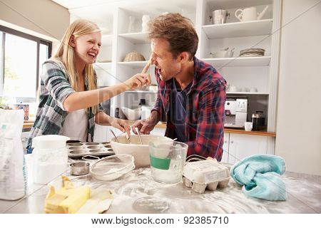 Father and daughter making a cake together