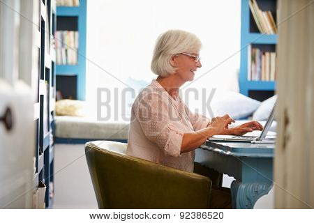 Senior Woman At Desk Working In Home Office With Laptop