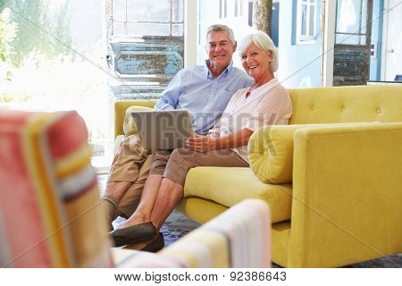 Senior Couple At Home In Lounge Using Laptop Computer