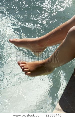 Young Girl's Feet Dangling Over Water
