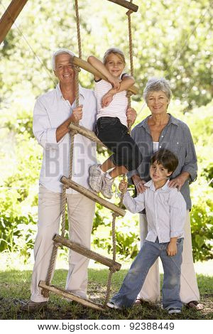 Grandchildren And Grandparents Standing By Tree House In Garden