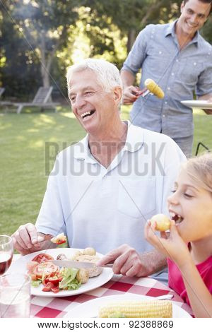 Extended Family Enjoying Barbeque In Garden Together