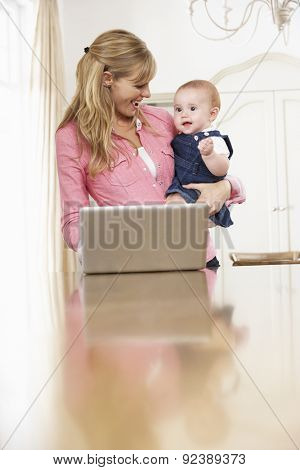 Mother Holding Baby Daughter Whilst Using Laptop