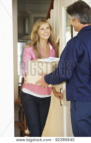Woman Signing For Package Delivered By Courier