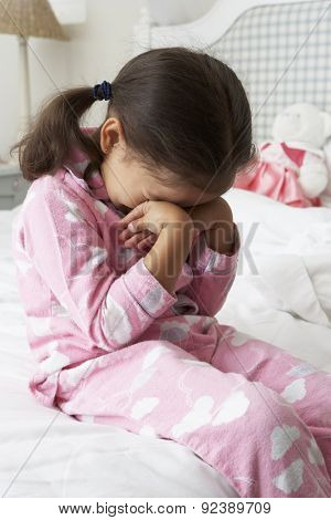 Tired Young Girl Wearing Pajamas Sitting On Bed
