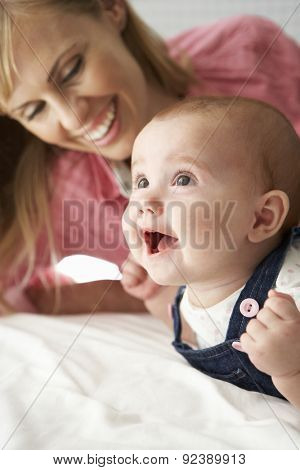Mother With Cute Baby Girl Playing On Bed
