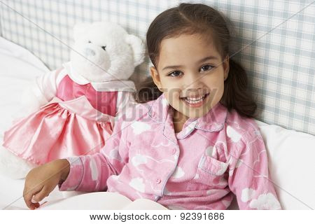 Young Girl Wearing Pajamas In Bed Reading Book