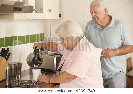 Retired Senior Couple In Kitchen Making Hot Drink Together