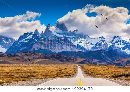 The highway crosses the Patagonia and leads to snow-capped peaks of Mount Fitzroy. Over the road flying flock of Andean condors