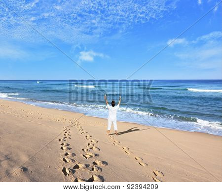 Huge beautiful beach on the Atlantic coast. Middle-aged woman dressed in white doing yoga. The seaside resort of Sintra