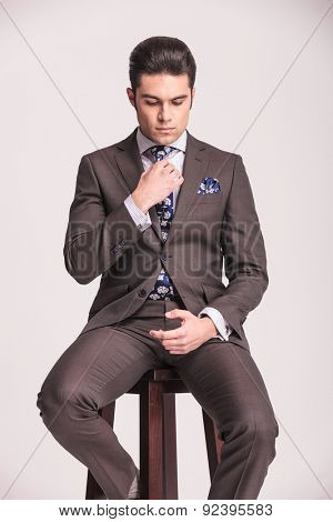 Attractive young business man sitting on a stool while fixing his tie. He is looking down.