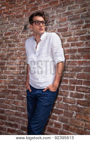 Portrait of a handsome fashion man leaning on a brick wall while holding his hands in pockets.