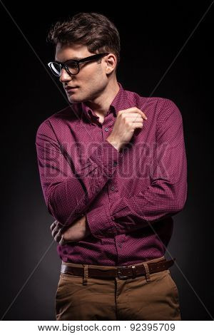 Young casual man standing on studio background while looking down to his side.
