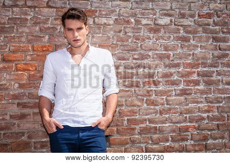Attractive young casual man leaning on a brick wall while holdinh his hands in pockets.