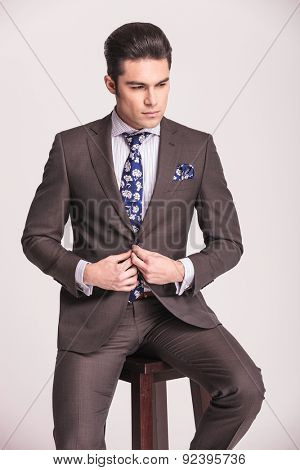 Handsome business man looking down while closing his suit. He is sitting on a brown chair.